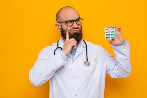 Uomo barbuto dottore in camice bianco con stetoscopio intorno al collo con gli occhiali che tengono blister con pillole guardando in alto perplesso