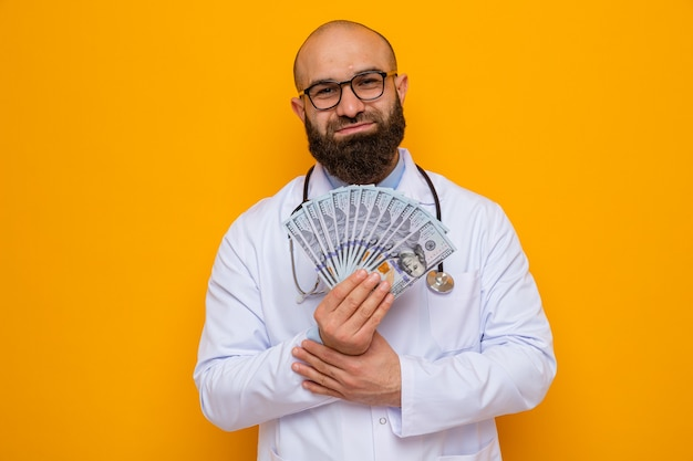 Bearded man doctor in white coat with stethoscope around neck wearing glasses holding cash looking at camera smiling happy and pleased standing over orange background