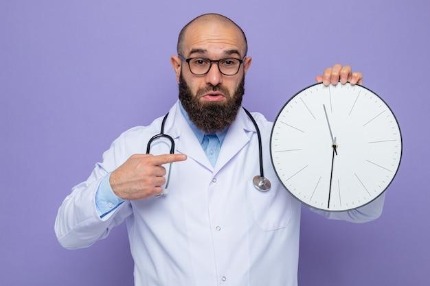Medico uomo barbuto in camice bianco con stetoscopio intorno al collo con gli occhiali che tengono l'orologio puntato con il dito indice con espressione confusa