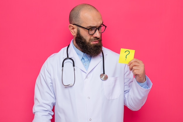 Bearded man doctor in white coat with stethoscope around neck wearing glasses holding reminder paper with question mark looking at it with serious face standing over pink background