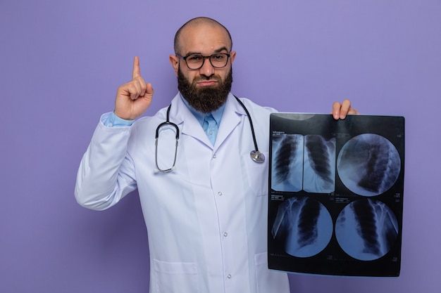Bearded man doctor in white coat with stethoscope around neck wearing glasses holding x-ray looking at camera with confident expression showing index finger standing over purple background