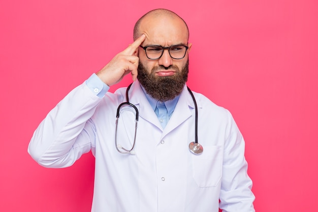 Bearded man doctor in white coat with stethoscope around neck wearing glasses looking aside confused pointing with index finger at his temple