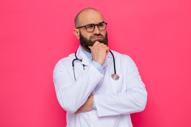 Bearded man doctor in white coat with stethoscope around neck wearing glasses looking aside with hand on his chin thinking with serious face standing over pink background