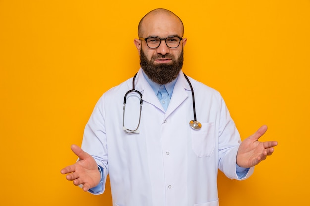 Bearded man doctor in white coat with stethoscope around neck wearing glasses looking at camera smiling confident happy and positive raising arms standing over orange background
