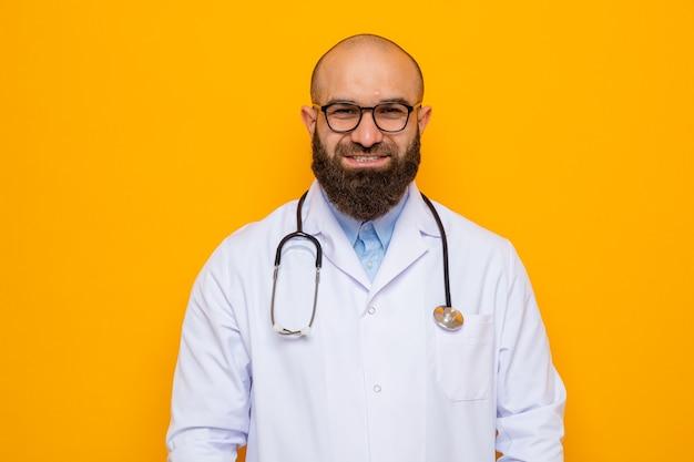 Uomo barbuto medico in camice bianco con stetoscopio intorno al collo con gli occhiali guardando la telecamera sorridente fiducioso in piedi su sfondo arancione