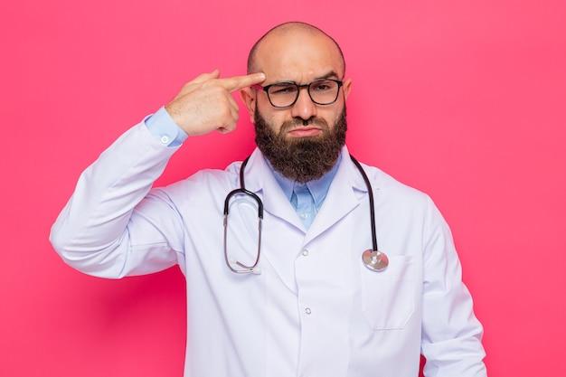 Medico uomo barbuto in camice bianco con stetoscopio intorno al collo con gli occhiali che guarda l'obbiettivo con faccia accigliata che punta con il dito indice alla tempia in piedi su sfondo rosa