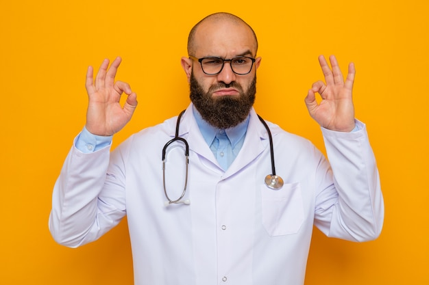 Bearded man doctor in white coat with stethoscope around neck wearing glasses looking confident showing ok sign standing over orange background