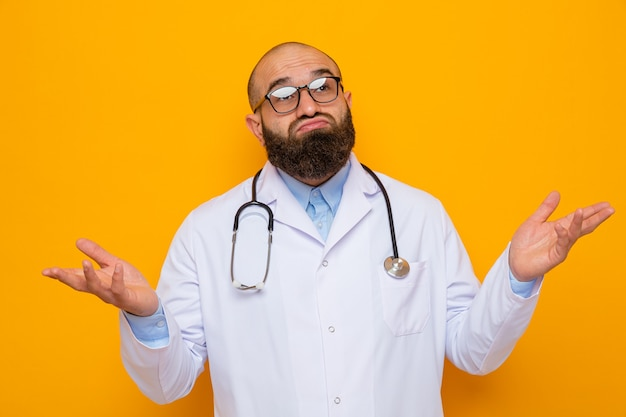 Bearded man doctor in white coat with stethoscope around neck wearing glasses looking confused spreading arms to the sides having no answer