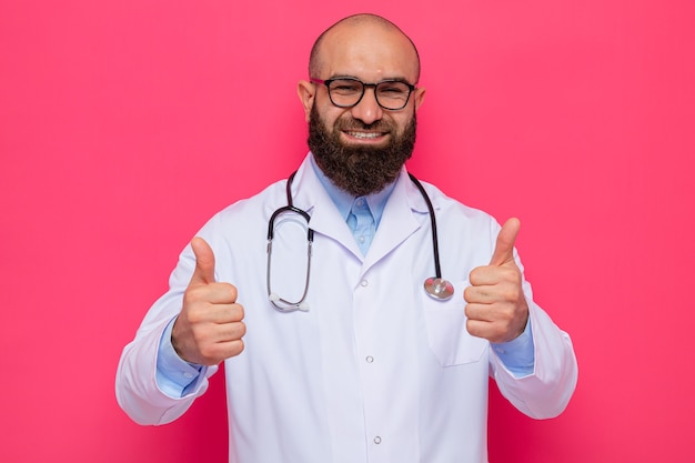 Bearded man doctor in white coat with stethoscope around neck wearing glasses looking smiling cheerfully showing thumbs up