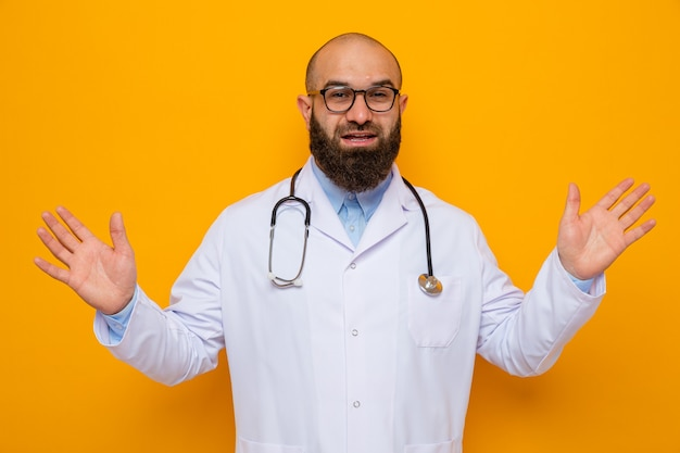 Bearded man doctor in white coat with stethoscope around neck wearing glasses looking smiling cheerfully spreading arms to the sides