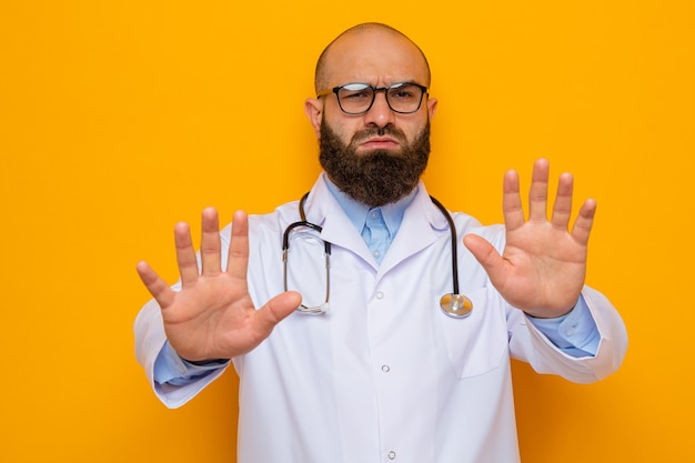 Bearded man doctor in white coat with stethoscope around neck wearing glasses looking with serious face making stop gesture with hands
