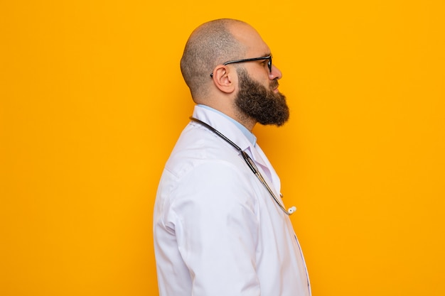 Uomo barbuto dottore in camice bianco con stetoscopio intorno al collo con gli occhiali in piedi di lato con faccia seria su sfondo arancione orange