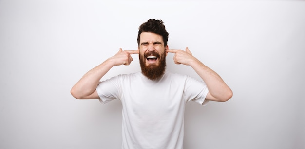 Bearded man doesn't want to hear anything. covers his years and screams.