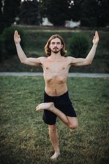 Bearded man doing yoga in the green park