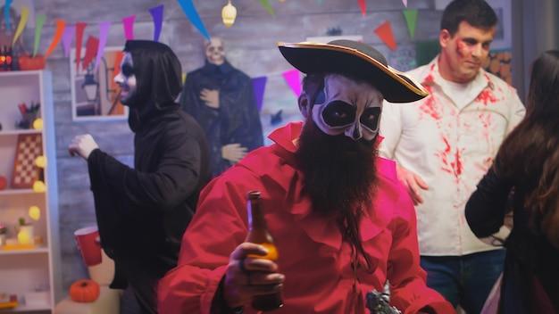 Бородатый мужчина, одетый как пират, празднует хэллоуин с группой друзей, замаскированных под разных монстров