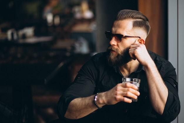 Bearded man drinking in a bar