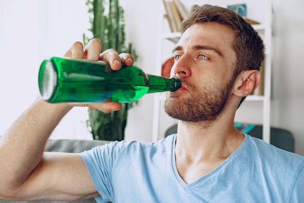 Bearded man drinking beer from the bottle while sitting on sofa at home