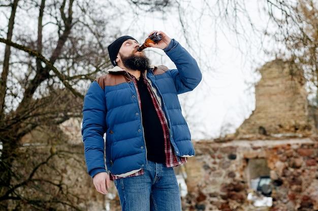 Бородатый мужчина пьет пиво зимой в парке