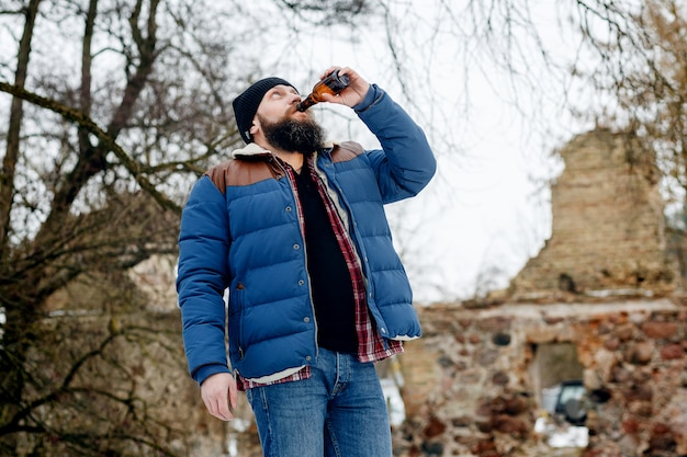 Bearded man drinking beer in winter in the park