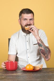 朝のコーヒーとトーストを手にトマトトーストとプレートカップで朝食を食べるひげを生やした男