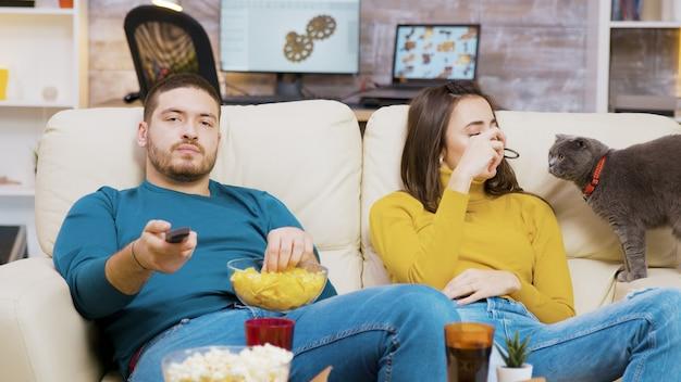Бородатый мужчина ест чипсы и с помощью пульта дистанционного управления переключает телеканалы, пока его девушка играет с кошкой.