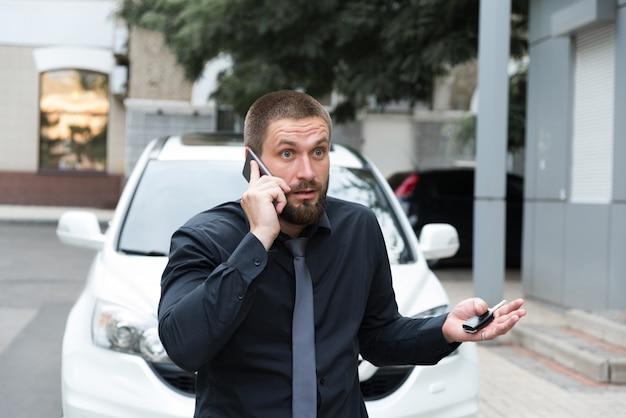 Bearded man emotionally talking on the phone near the car