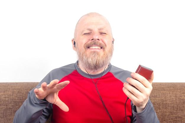 あごひげを生やした男性は、小さなヘッドホンのオーディオプレーヤーでお気に入りの音楽を聴くのを楽しんでいます。