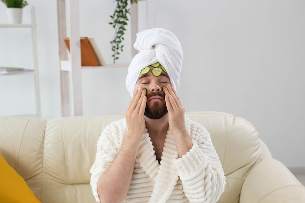 Бородатый мужчина наслаждается косметической маской на лице, сделанной из ломтиков огурца, мужского ухода за кожей и