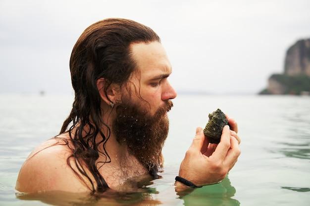 ライレイのビーチで独特の形の石を調べるひげを生やした男
