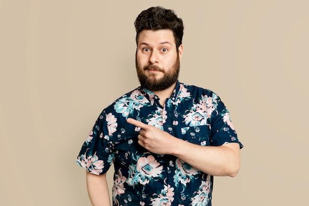 Uomo barbuto in camicia estiva floreale che punta di lato