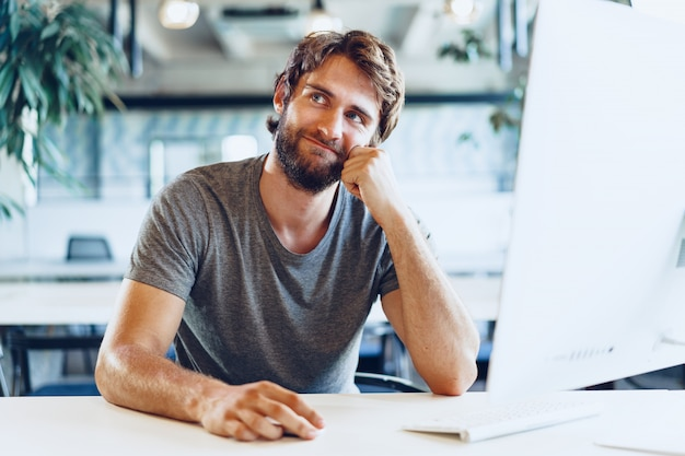 Bearded man freelancer using computer in a modern coworking place. freelance business concept