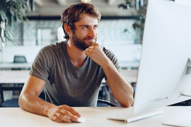 Bearded man freelancer using computer in a modern coworking place