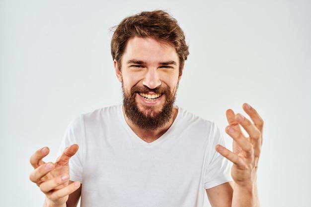 手で身振りで示すひげを生やした男トリミングビュー白いtシャツスタジオ感情明るい背景