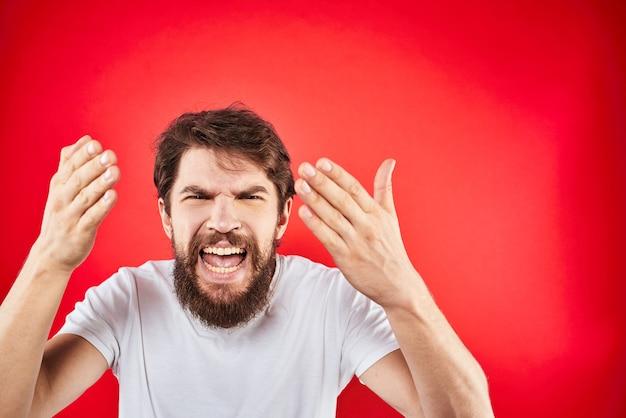 Бородатый мужчина жестикулирует руками в белой изолированной футболке