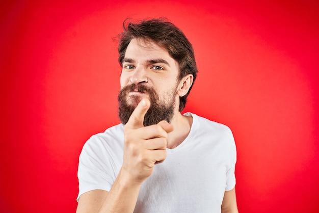 Бородатый мужчина жестикулируя руками белая футболка эмоции выражение лица агрессия красная изолированная стена.