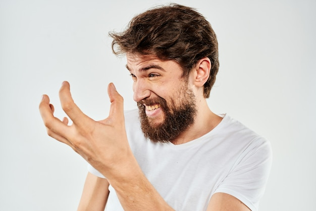 Бородатый мужчина жестикулирует руками белая футболка студия эмоции светлый фон