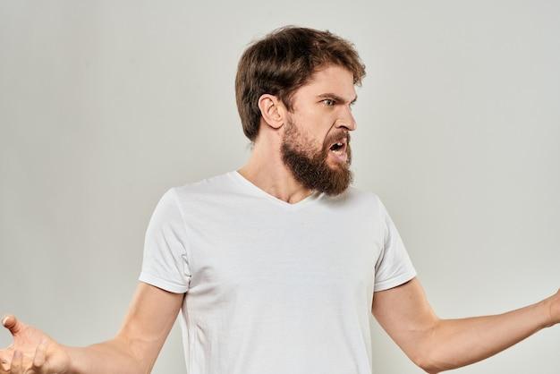 白いtシャツの攻撃性の明るい背景で彼の手で身振りで示すひげを生やした男