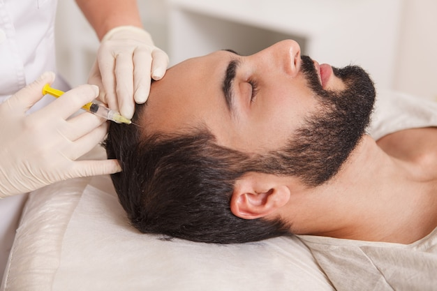 Bearded man getting anti hair loss treatment by beautician