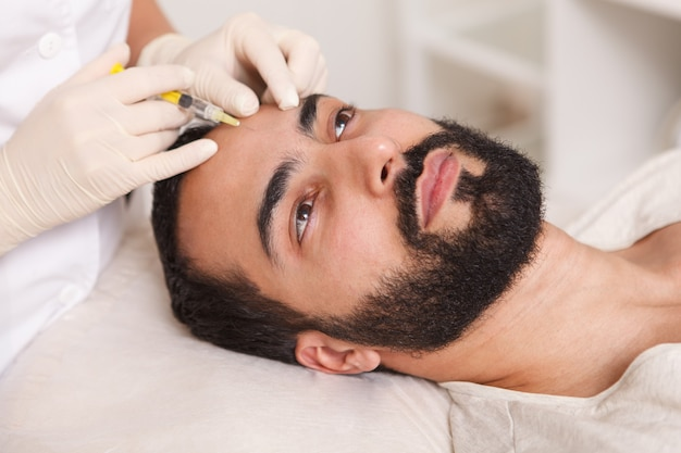 Bearded man getting face filler injections by cosmetologist