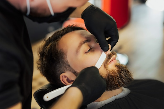 Bearded man getting face treatment after black mask at barber shop