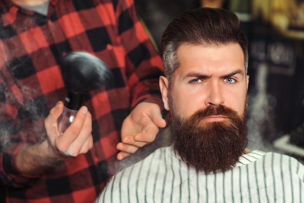 Бородатый мужчина стрижка парикмахером. брутальный парень сидит в парикмахерской. винтажная парикмахерская, бизнес.