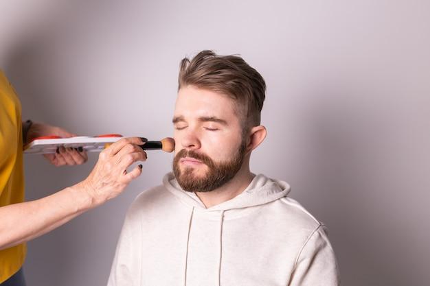 Бородатый мужчина получает макияж руки визажиста с помощью кисти