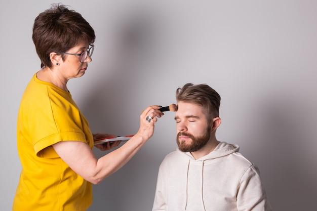 Бородатый мужчина делает макияж, визажист женщина работает с кистью