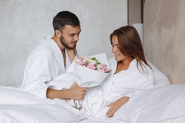Bearded man gives a bouquet of flowers to a woman in a white bed