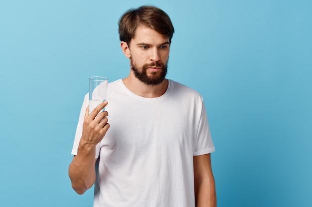 Бородатый мужчина стакан воды синий фон