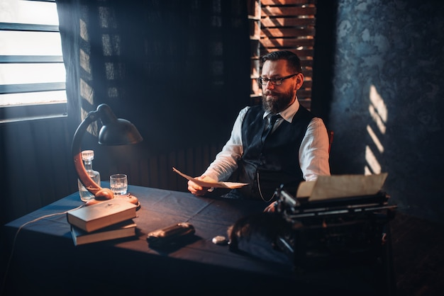 Bearded man in glasses reads handwritten text