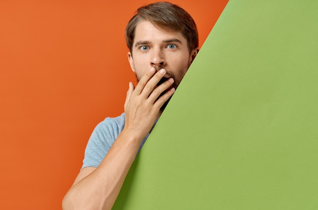 Bearded man in gray t-shirt green mockup poster orange background. high quality photo