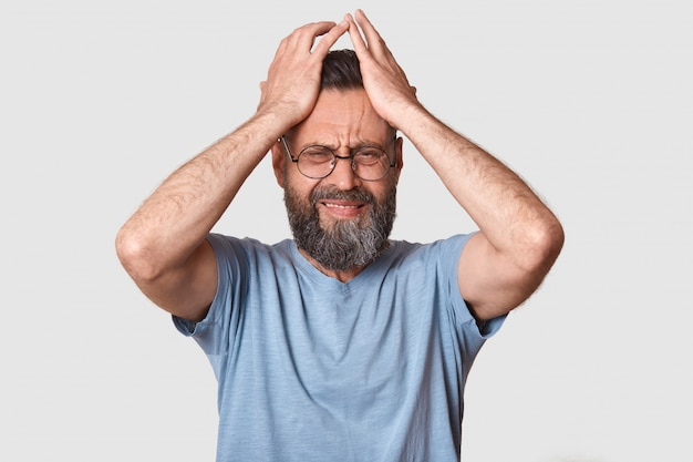 Bearded man in gray t shirt, has round eyewear, keeps hand on head, grimaced, has problems, being in bad mood, has terrible headache