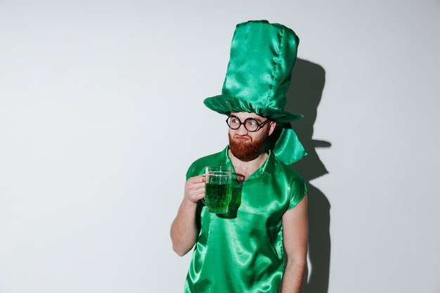 Bearded man in green costume and eyeglasses holding cup