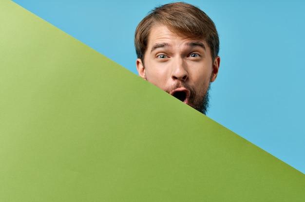 マーケティングの青い背景の手にひげを生やした男の緑の紙